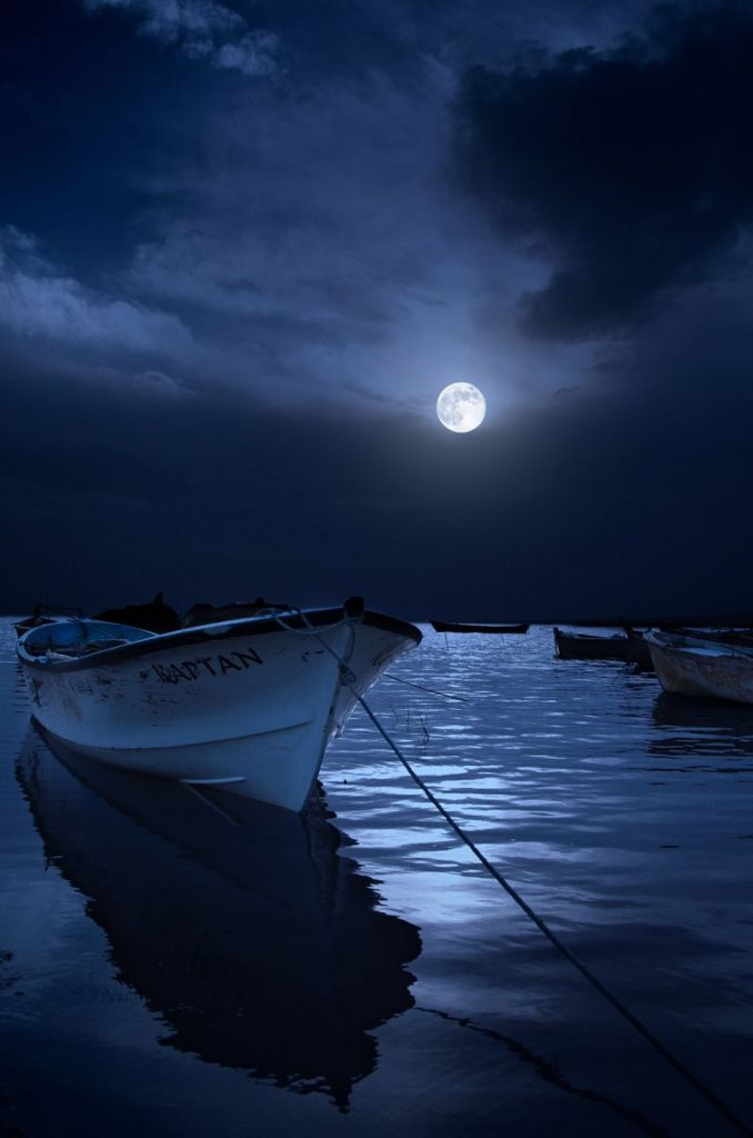 full moon and boat in harbor
